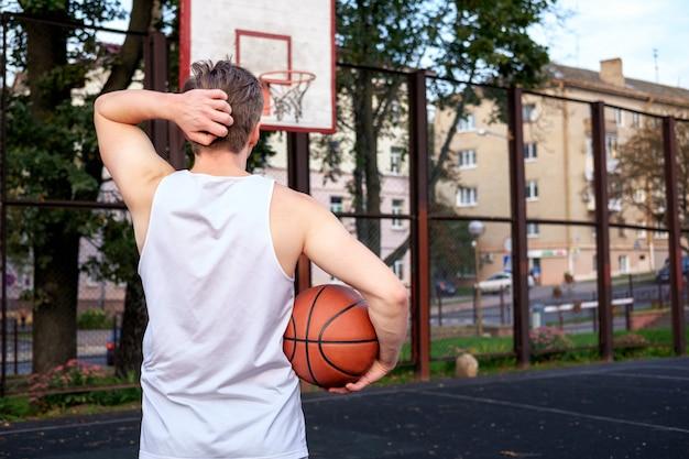 Hombre preparando jugar baloncesto, permanecer delante de la canasta y sosteniendo la pelota