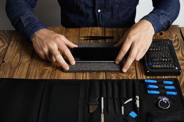 El hombre está preparando el teléfono inteligente para su restauración reparación de trabajos de servicio de dispositivos electrónicos
