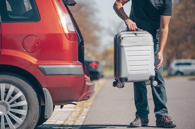 Hombre preparándose para las vacaciones, vacaciones, poner un equipaje en el maletero del coche, tiempo libre, concepto de turismo