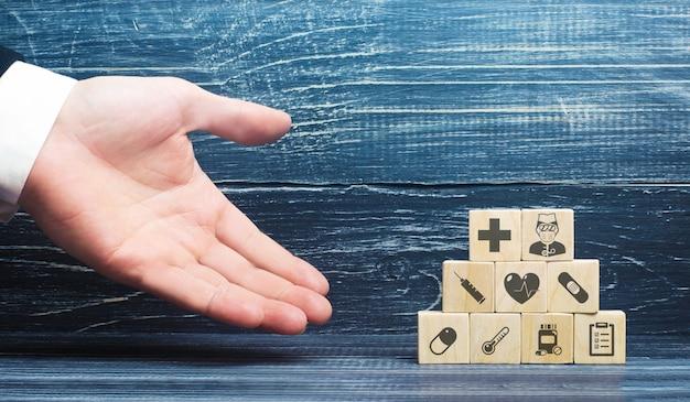 Un hombre presenta bloques con atributos médicos. concepto de seguro médico y sanitario