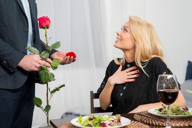 Hombre presentando una caja de regalo y una flor a una mujer rubia sorprendida en la mesa