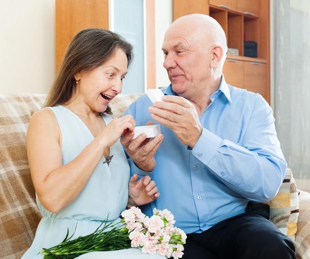 Hombre presentando mujer sorprendida joya