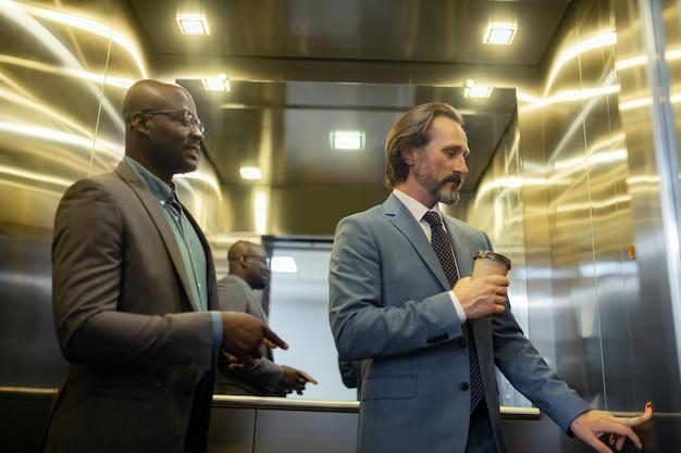 Hombre presionando el botón. empresario canoso sosteniendo café para llevar presionando el botón en el ascensor