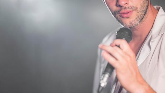 Hombre de primer plano cantando en el micrófono