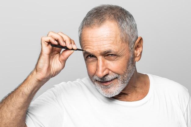 Hombre de primer plano depilarse las cejas