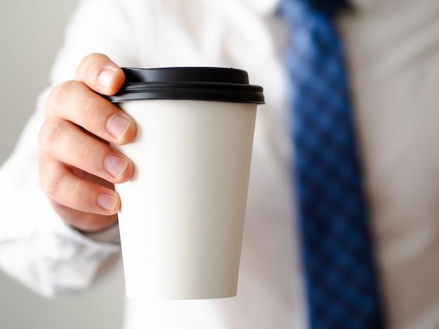 Hombre de primer plano con maqueta de taza de café