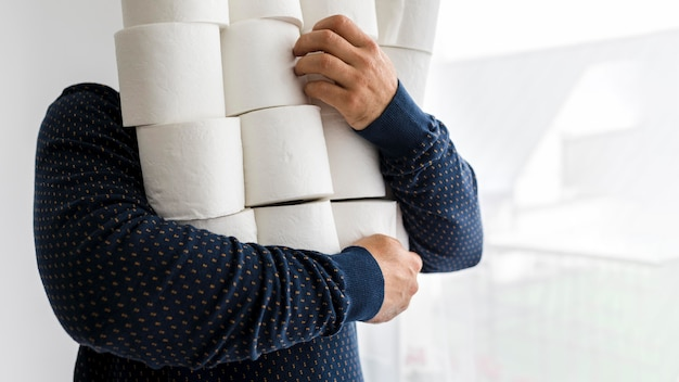 Hombre de primer plano con pila de papel higiénico
