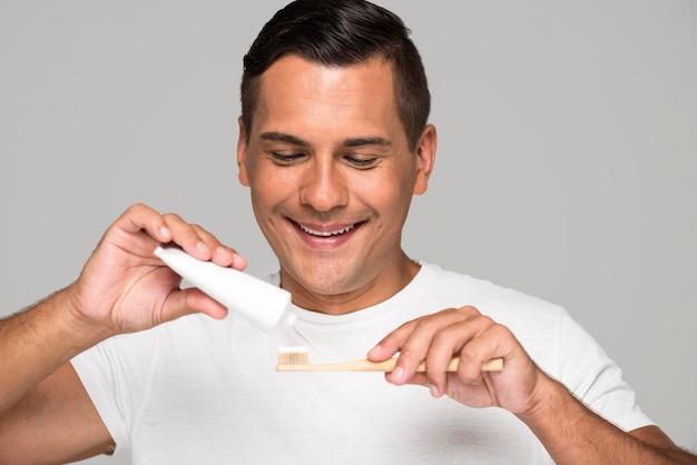 Hombre de primer plano poniendo pasta de dientes en el cepillo de dientes