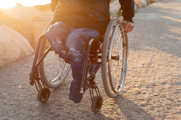 Hombre de primer plano en silla de ruedas en la playa