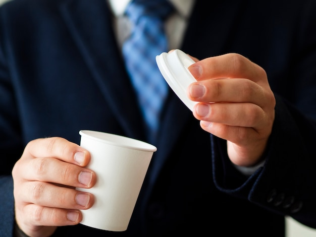 Hombre de primer plano sosteniendo maqueta de taza de café