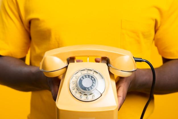 Hombre de primer plano con teléfono antiguo