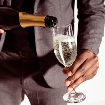 Hombre de primer plano vertiendo champán en botella