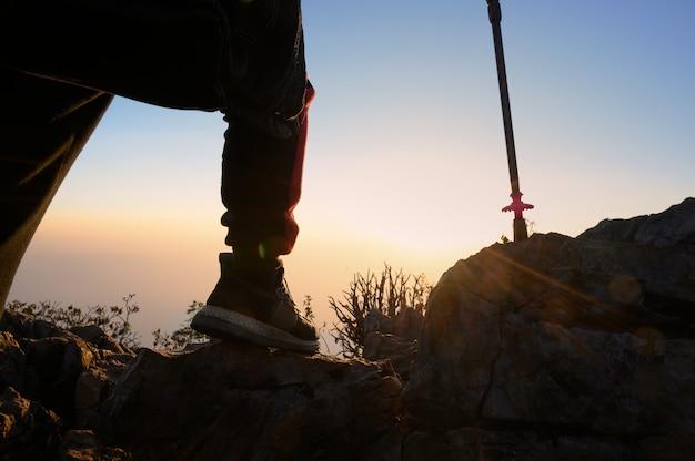 Hombre del primer que camina en la montaña de la silueta de la puesta del sol con concepto de la aventura de la forma de vida del viaje.