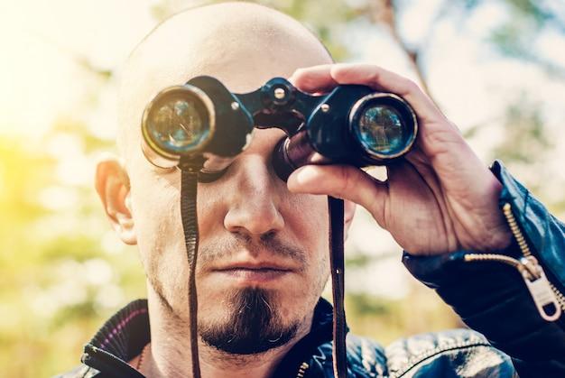 Hombre con prismáticos vintage al aire libre