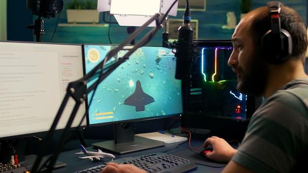 Hombre pro streamer jugando videojuegos de disparos espaciales durante la competencia en línea usando una configuración profesional con chat abierto
