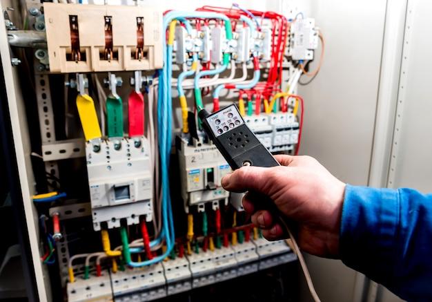Hombre probando cables e interruptores en caja eléctrica