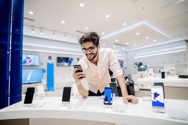 Hombre probando nuevo teléfono inteligente. interior de la tienda de tecnología.