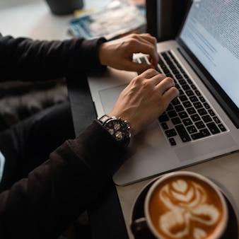 Hombre profesional independiente en ropa negra con un reloj caro se sienta en un café, bebe café y trabaja en una computadora portátil