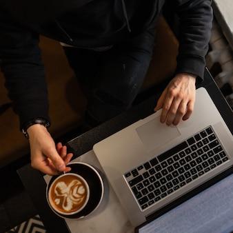 Hombre profesional en ropa negra se sienta en un café, bebe café y trabaja en la computadora portátil, vista superior