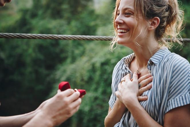 Hombre proponiendo a su mujer con una caja roja