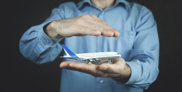 El hombre protege el avión de juguete. seguro de viaje
