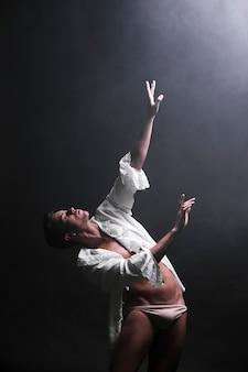 Hombre provocativo bailando en la oscuridad