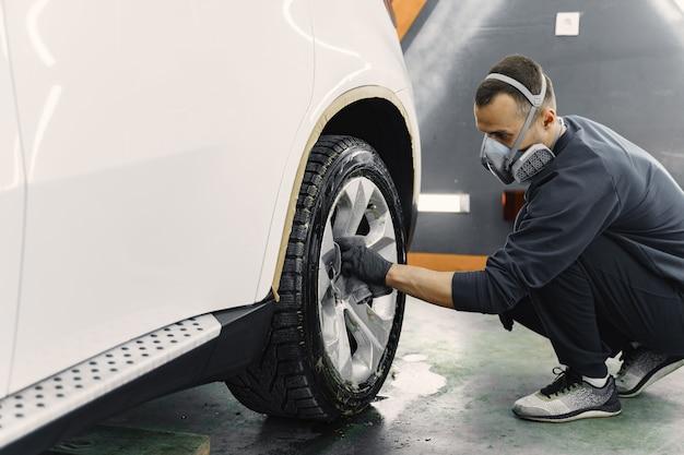 Hombre pulir un auto en un garaje