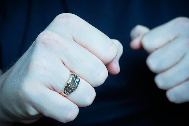 El hombre puso puños amenazantes con un anillo. azul tonificado.
