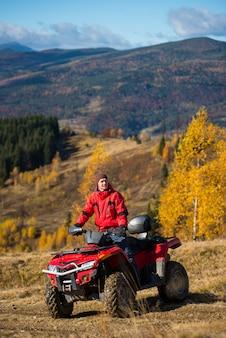 Hombre en quad en las montañas en un fondo borroso poderosas montañas