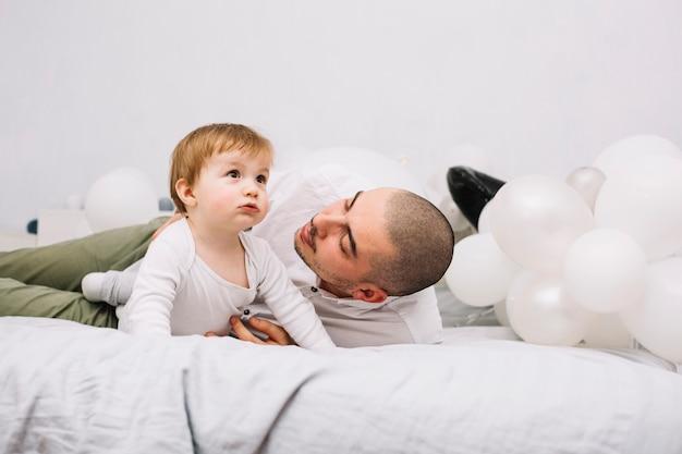 Hombre que abraza al pequeño bebé en cama cerca de los globos