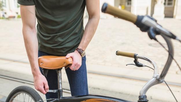Hombre que ajusta el asiento de la bicicleta
