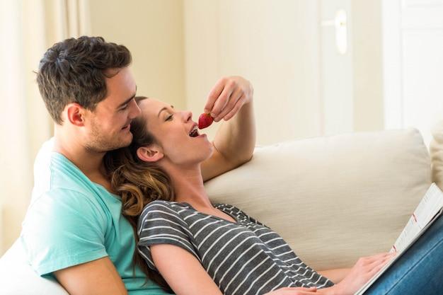 Hombre que alimenta una fresa a la mujer en la sala de estar
