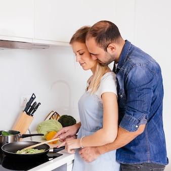 Hombre que ama a su esposa cocinando comida en la cocina de inducción en la cocina