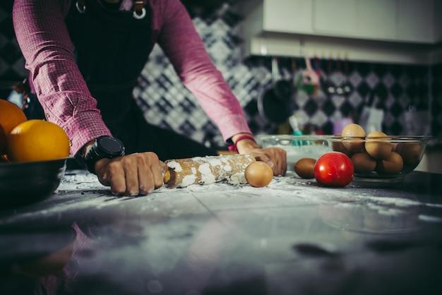 Hombre que amasa la pasta hecha en casa de la pizza en la cocina. concepto de cocina