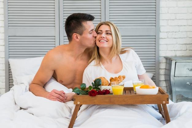 Hombre que besa a la mujer sonriente en cama cerca del desayuno a bordo