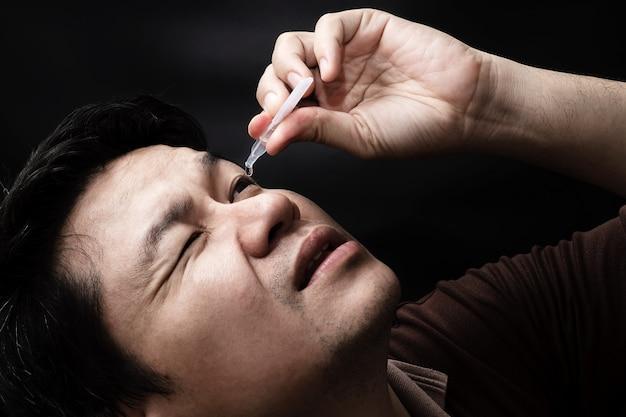 Hombre que cae la medicina de la gota del ojo que cura su dolor del ojo con el fondo negro