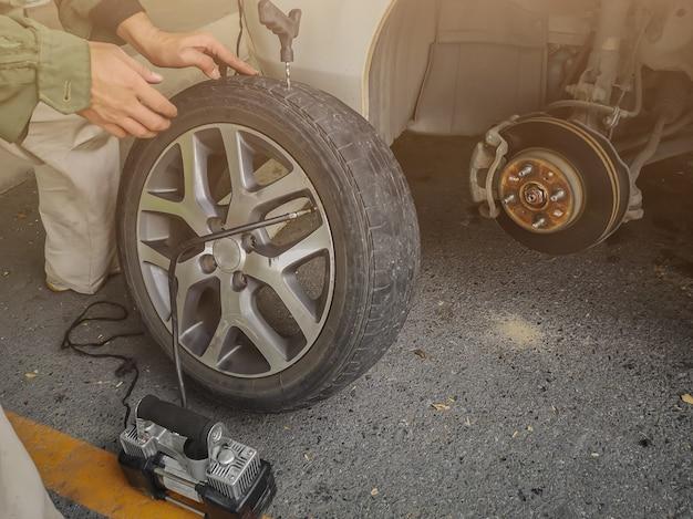 Hombre que cambia la rueda de repuesto en una carretera. parche y tapón en el neumático.