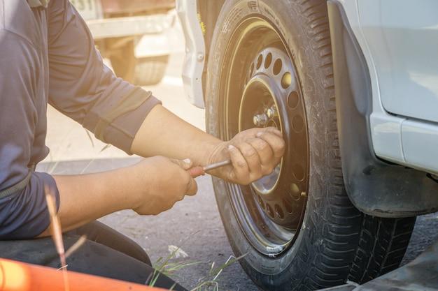 Hombre que cambia la rueda de repuesto en una carretera.