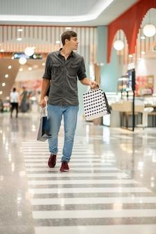 Un hombre que camina por el centro comercial lleva una gran cantidad de paquetes con compras en ambas manos, buscando nuevas compras. el concepto de compras para hombres. día de venta