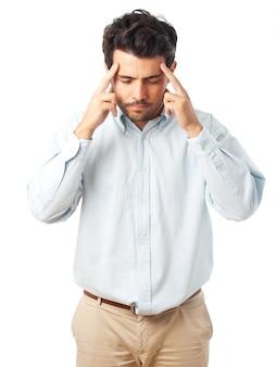 Hombre que se concentra con los dedos en el templo sobre un fondo blanco