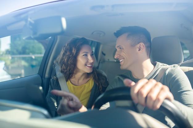 El hombre que conduce y al lado de la mujer usan cinturones de seguridad