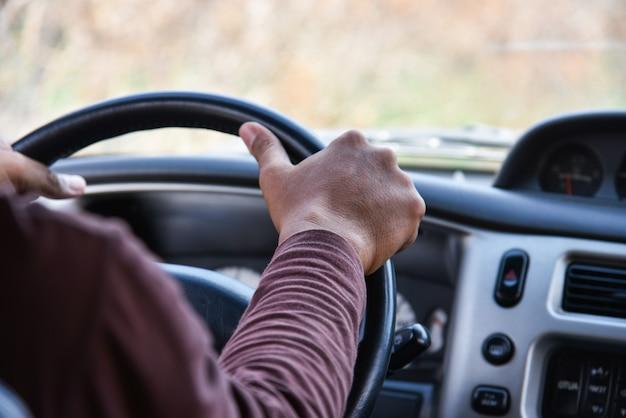 Hombre que conduce un automóvil / conductor con las manos en el volante que conduce mi automóvil en la carretera