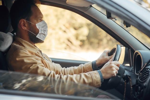 Un hombre que conduce un automóvil se pone una máscara médica durante una epidemia, un taxista con una máscara