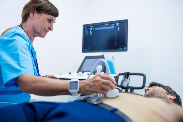 El hombre que consigue ultrasonido de un abdomen del médico