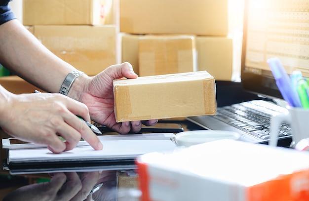 Hombre que controla la orden de compra en línea y escribe en la entrega en la caja del paquete trabajando en la oficina en casa.