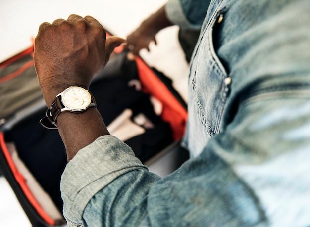 Hombre que controla el tiempo del reloj en la habitación de hotel