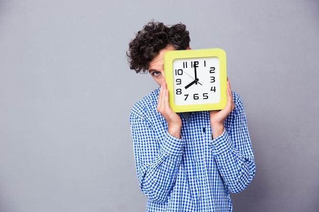Hombre que cubre la cara con reloj y mirando hacia el frente