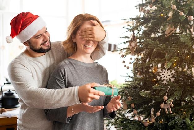 El hombre que cubre los ojos de su esposa para un regalo de navidad