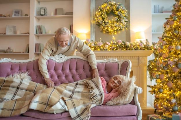 Hombre que cubre a su esposa durmiendo con un plaid
