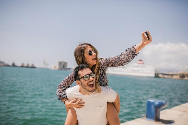 Hombre que da a su novia a cuestas paseo tomando selfie en el teléfono celular cerca del mar